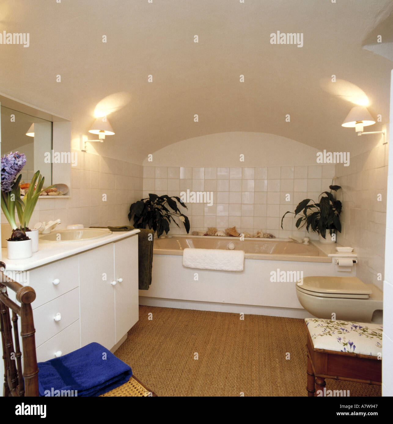 Sisal Carpet And Green Houseplants In White Tiled Basement Bathroom With  Lighted Wall Lights And Curved Ceiling