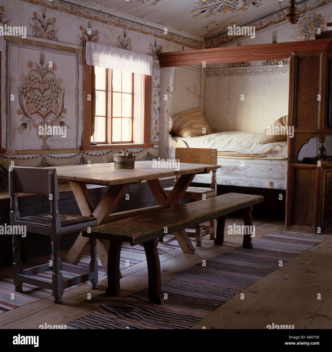 Rustic Wooden Table And Bench In Scandinavian Country Room With Simple  Four Poster Bed And Wall Paintings