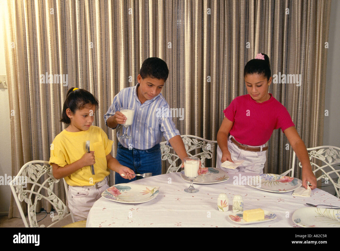 Three Hispanic Children One Brother And Two Sisters Set The Table For Family Dinner