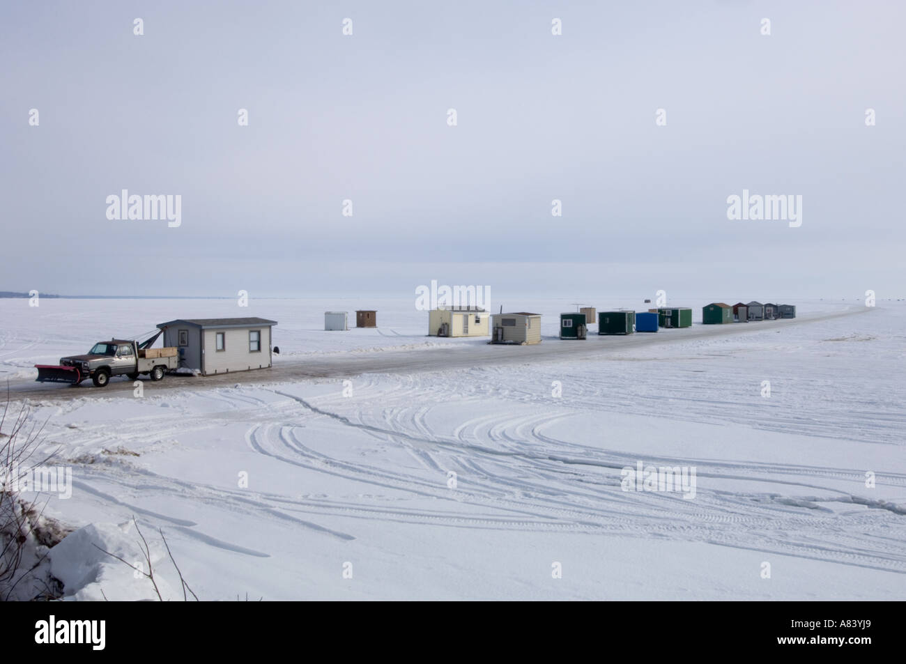 Ice fishing houses lined up waiting to be hauled off of for Lake mille lacs ice fishing