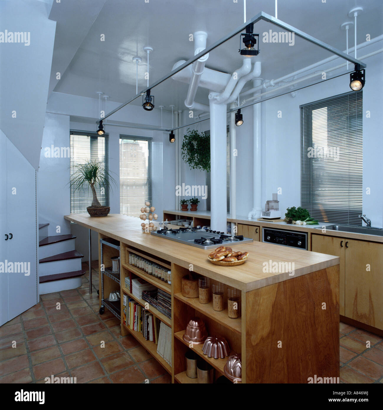 open shelving in wooden island unit below tubular lighting track in modern white loft conversion kitchen - Kitchen Lighting Track