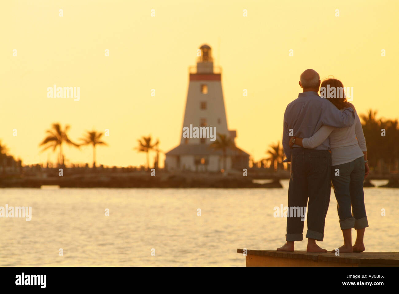 an-older-couple-watches-the-sun-set-by-a