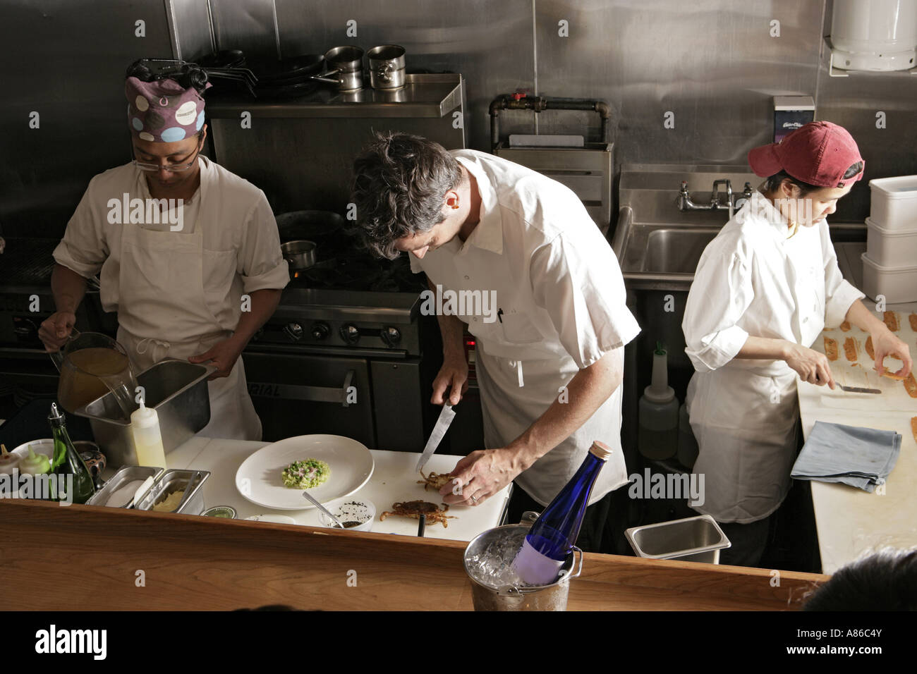 Three people working in kitchen front view stock photo for Amenagement cuisine de restaurant