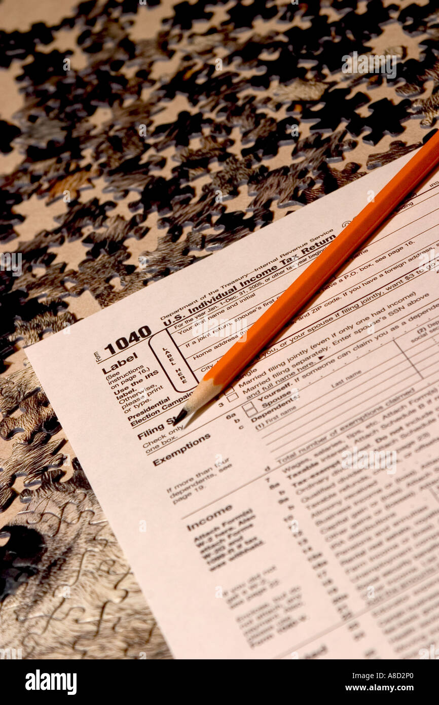 Income tax form 1040 on a puzzle with a chewed on broken pencil and income tax form 1040 on a puzzle with a chewed on broken pencil and puzzle pieces laying on top falaconquin