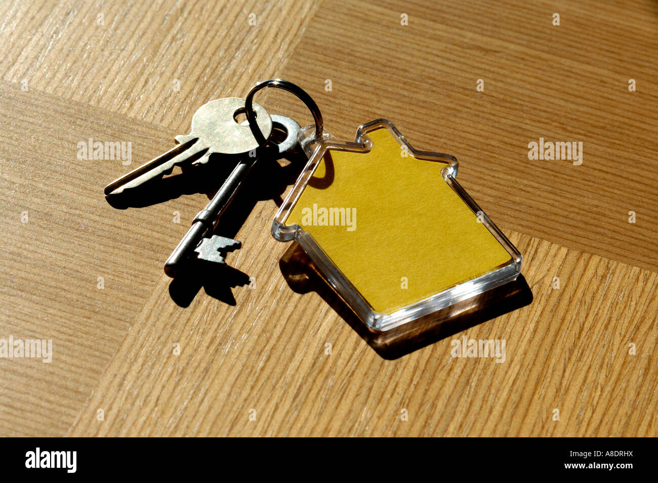 House keys and house shaped keyring on wooden table Stock ...