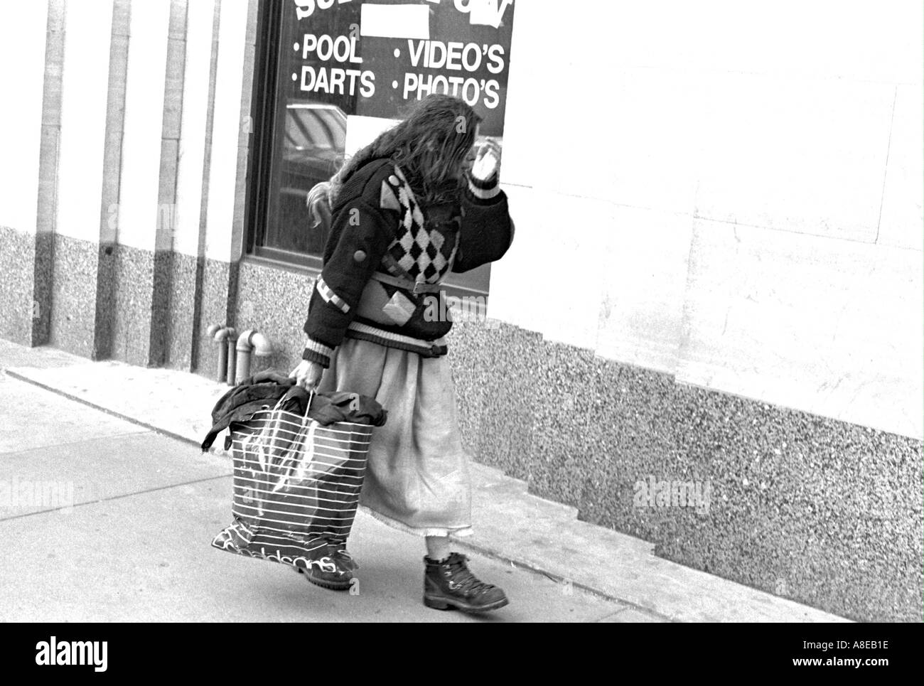 Homeless bag lady age 35 walking by pool hall with shopping bag ...