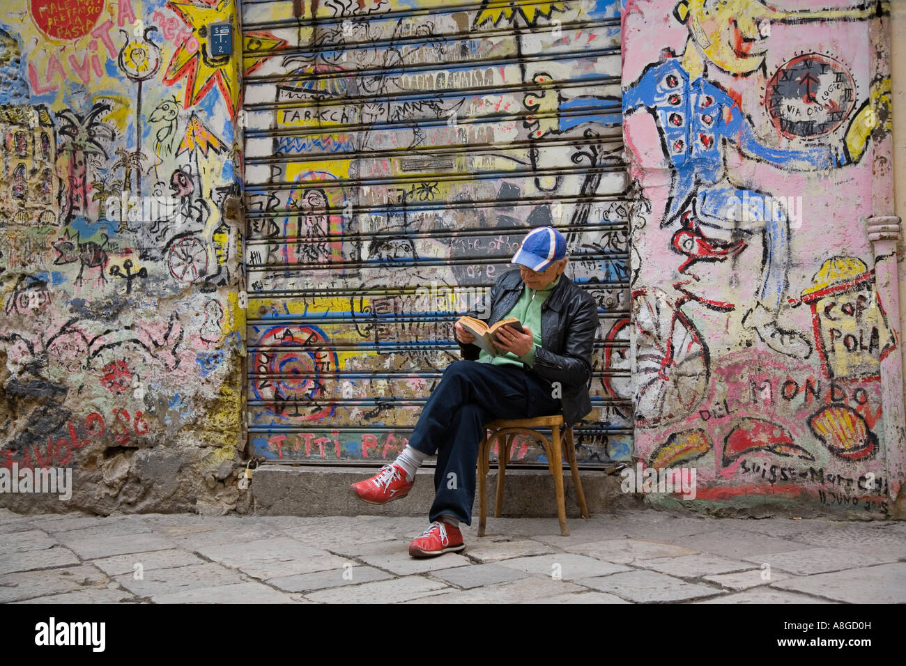 Graffiti wall reading - Man Reading Book In Front Of Graffiti Covered Wall On Neighborhood Street Via Dello Orologio Palermo Sicily Italy