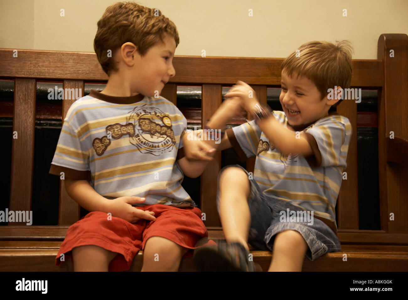 Two Young Boys Children Brothers Wearing Shorts And T Shirts Sitting On A Bench Playing Fighting Laughing NAOH CJWH