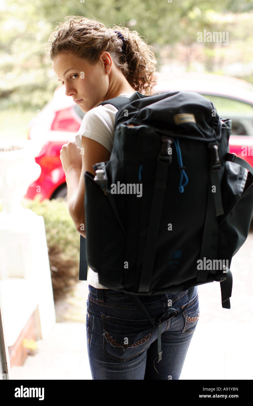 girl with rucksack on her back walking out the door Stock Photo