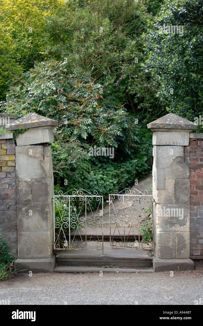 Old Stone Pillars : A garden gate with stone pillars and red brick wall uk