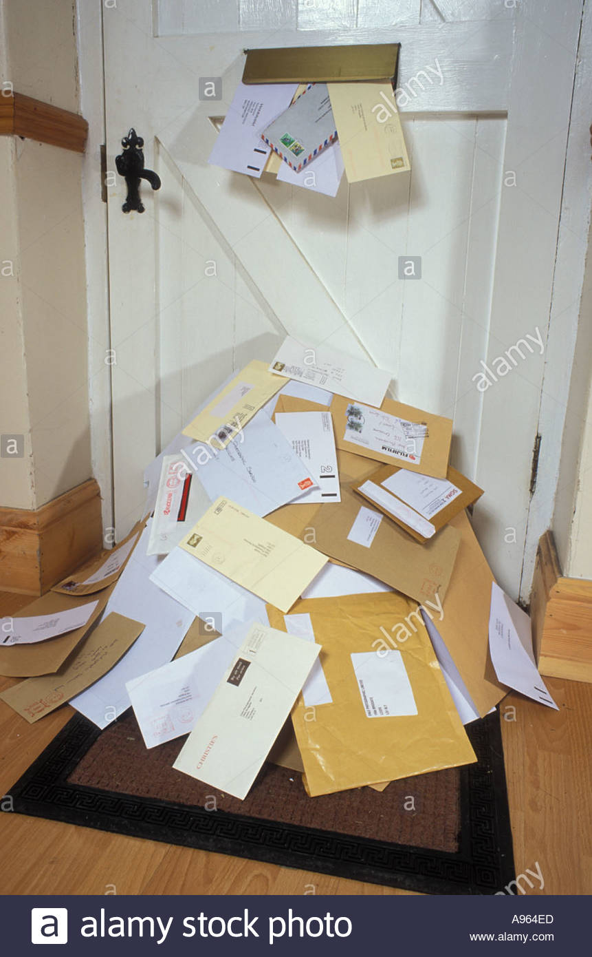 huge mound of letters and junk mail through letter box on hall mat uk