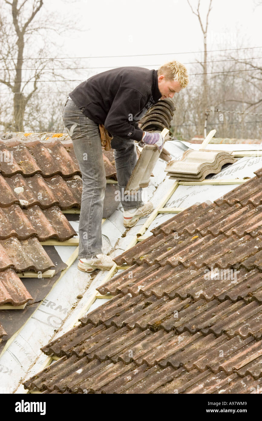 Stock Photo   a builder fitting tiles onto a roof of a home extension. A Builder Fitting Tiles Onto A Roof Of A Home Extension Stock