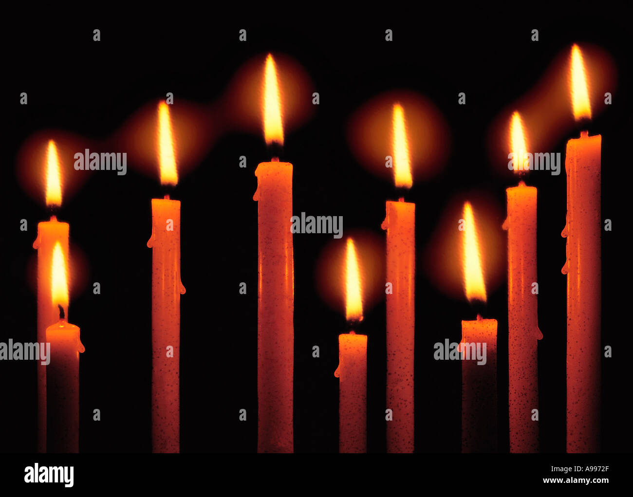 Close Up Of Nine Lit Candles Dripping Wax With A Halo Appearing ...