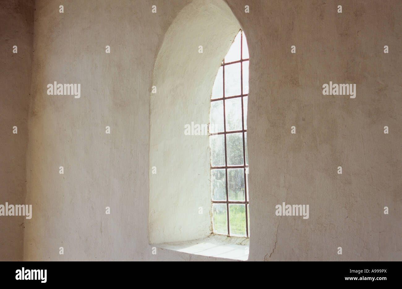 Interior view of small room or lobby or porch or hall or hallway with plain cream walls and square leaded arched window