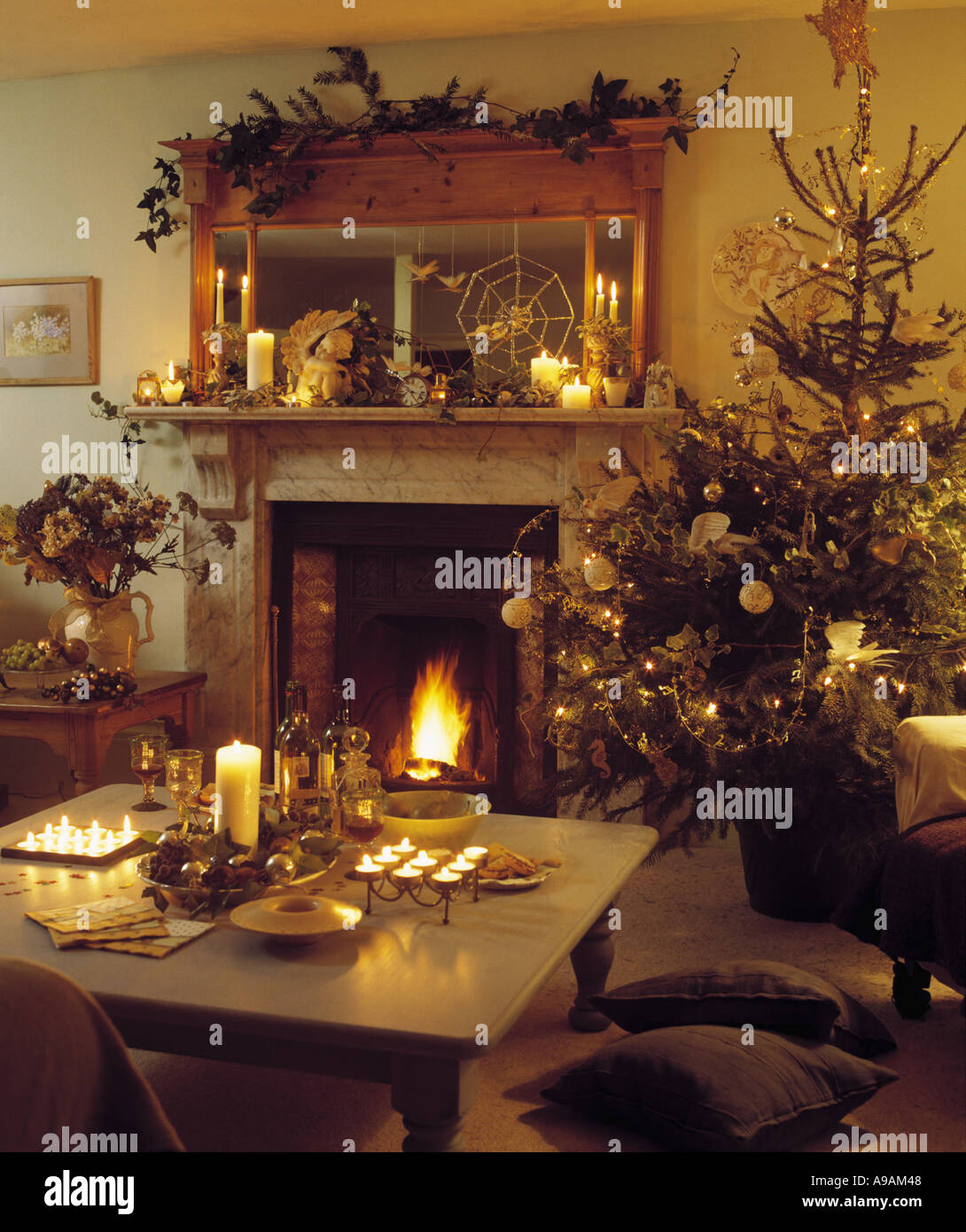 christmas tree beside fireplace with lighted fire in warm living