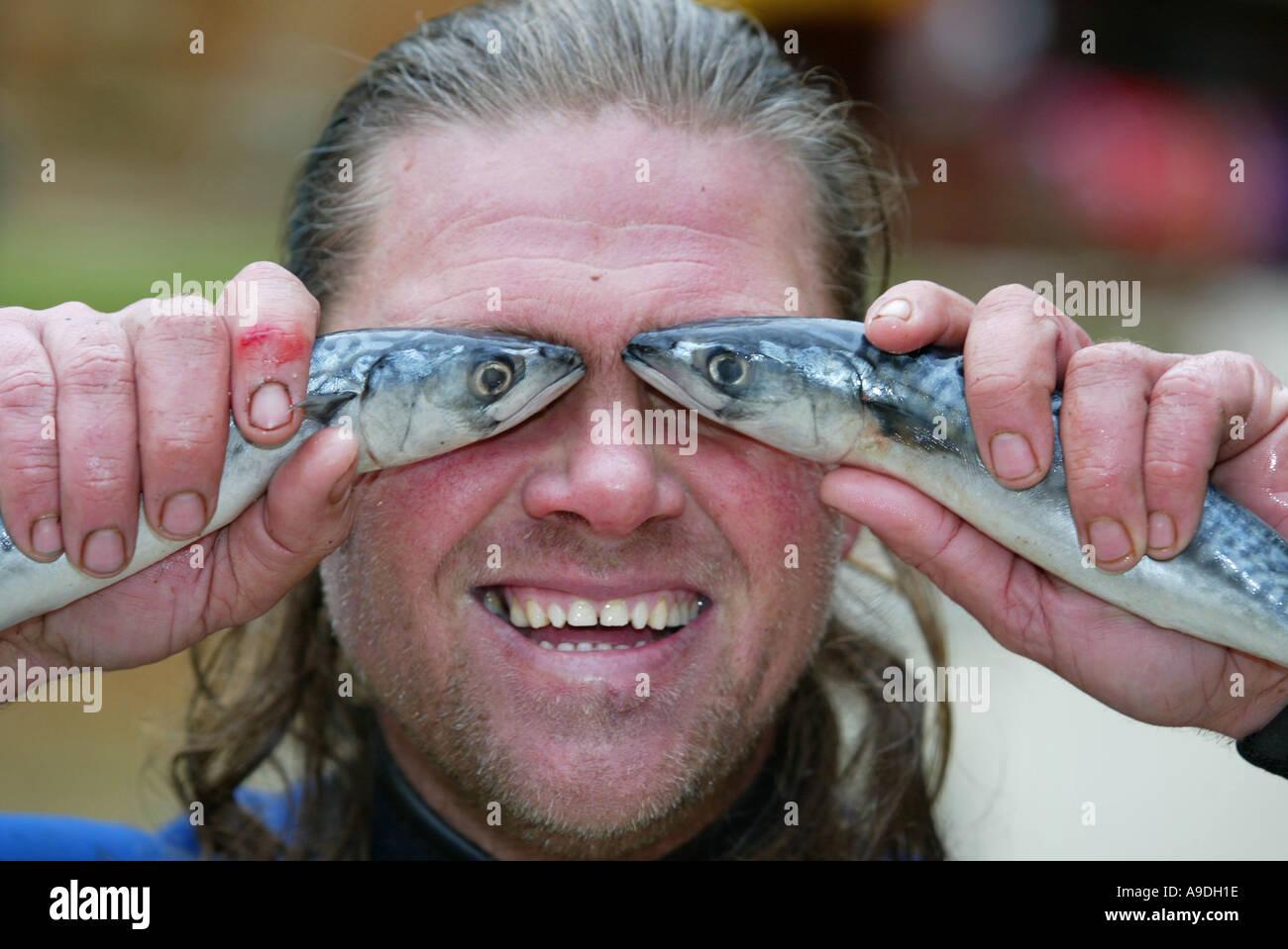 man holding up fishes fish eyes stock photo royalty free