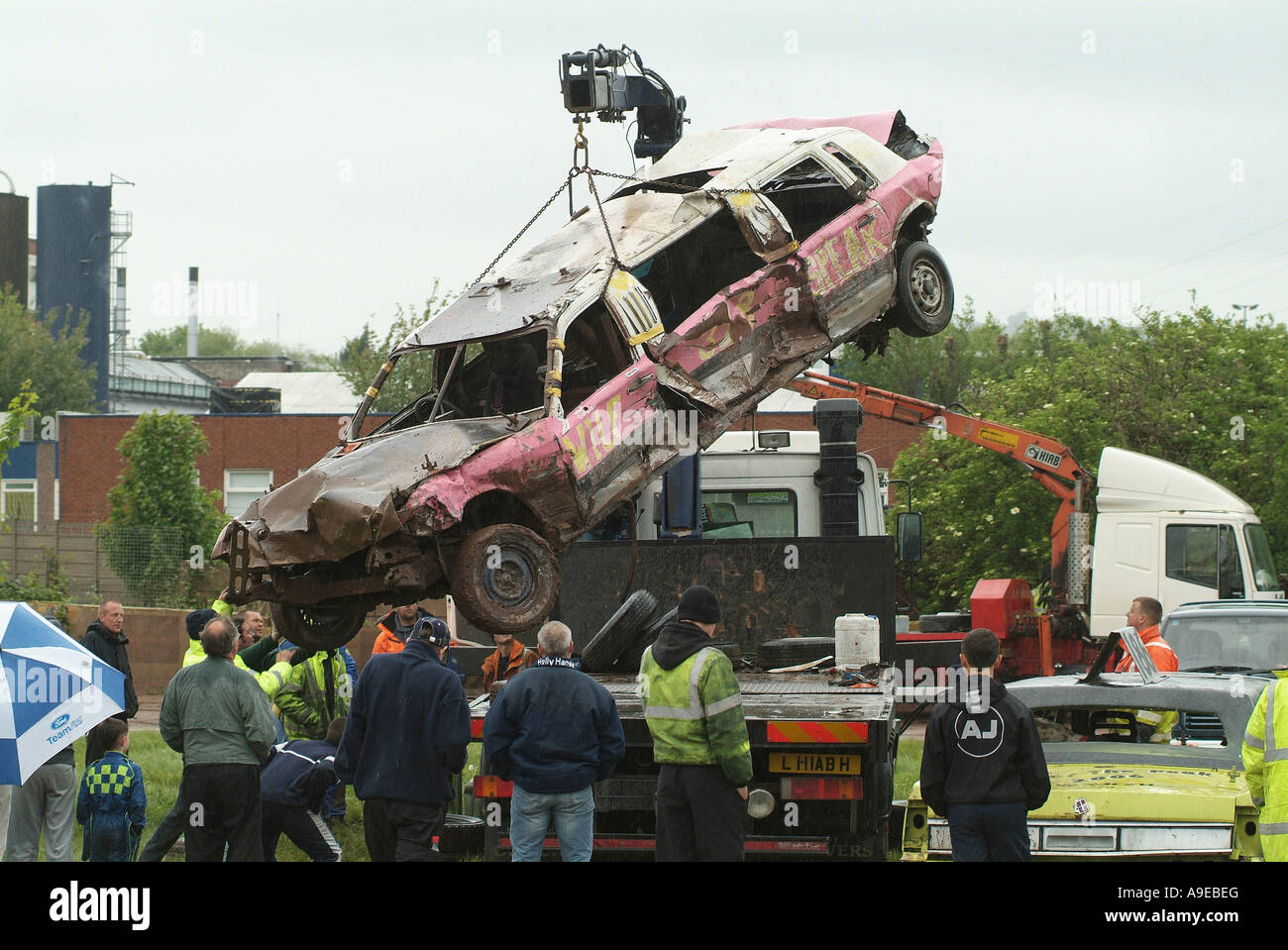 old limousine being lifted onto a truck after a demolition derby ...