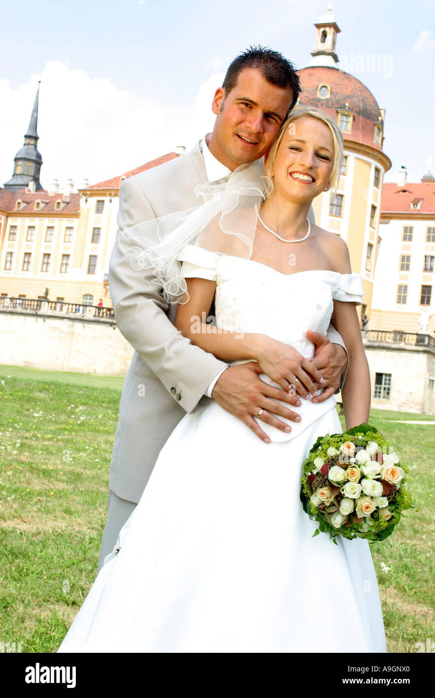 Young Wedding Couple Posing For Photography Groom Wearing Suit Bride Dress Standing Behing Bri