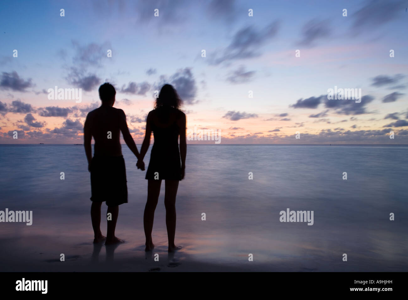 Silhouette of a couple holding hands at sunset Stock Photo ... for Couple Holding Hands Silhouette Sunset  270bof