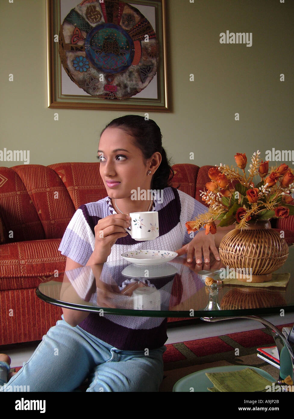 Ang99030 south asian indian girl wearing modern dress looking outside from the house and drinking tea model release 570