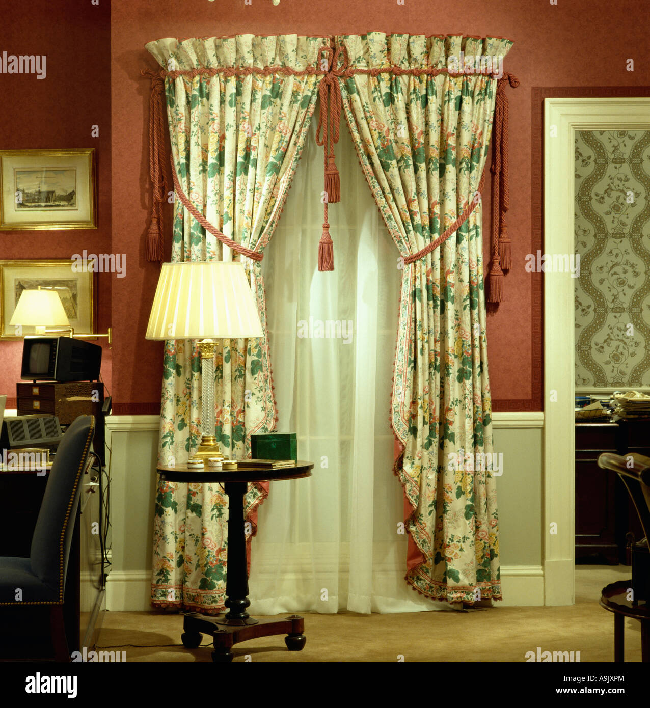 Red patterned curtains - Green And White Patterned Curtains With Red Trimmings Over White Voile Curtains Against Red Wall