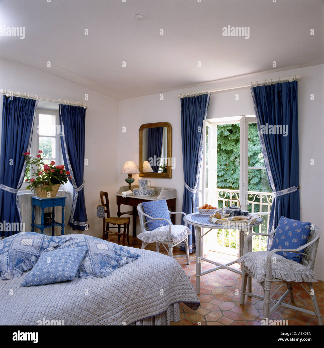 Blue cushions piled on bed in country bedroom with blue curtains at French  windows open on to the balcony. Blue cushions piled on bed in country bedroom with blue curtains