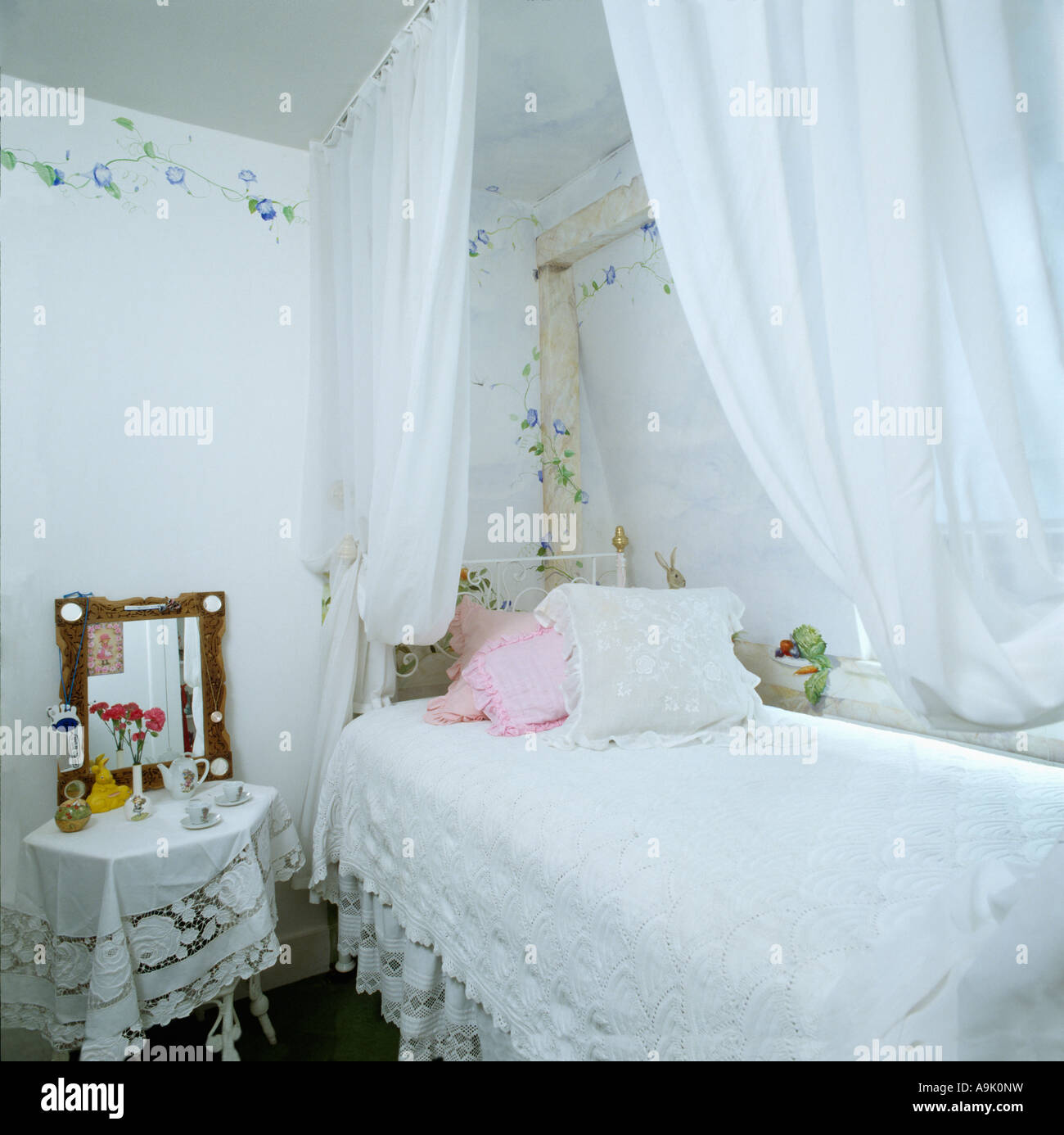 Stock Photo   White voile drapes above bed with white lace cover in small white  bedroom with stencilled blue floral border on the walls. White voile drapes above bed with white lace cover in small white