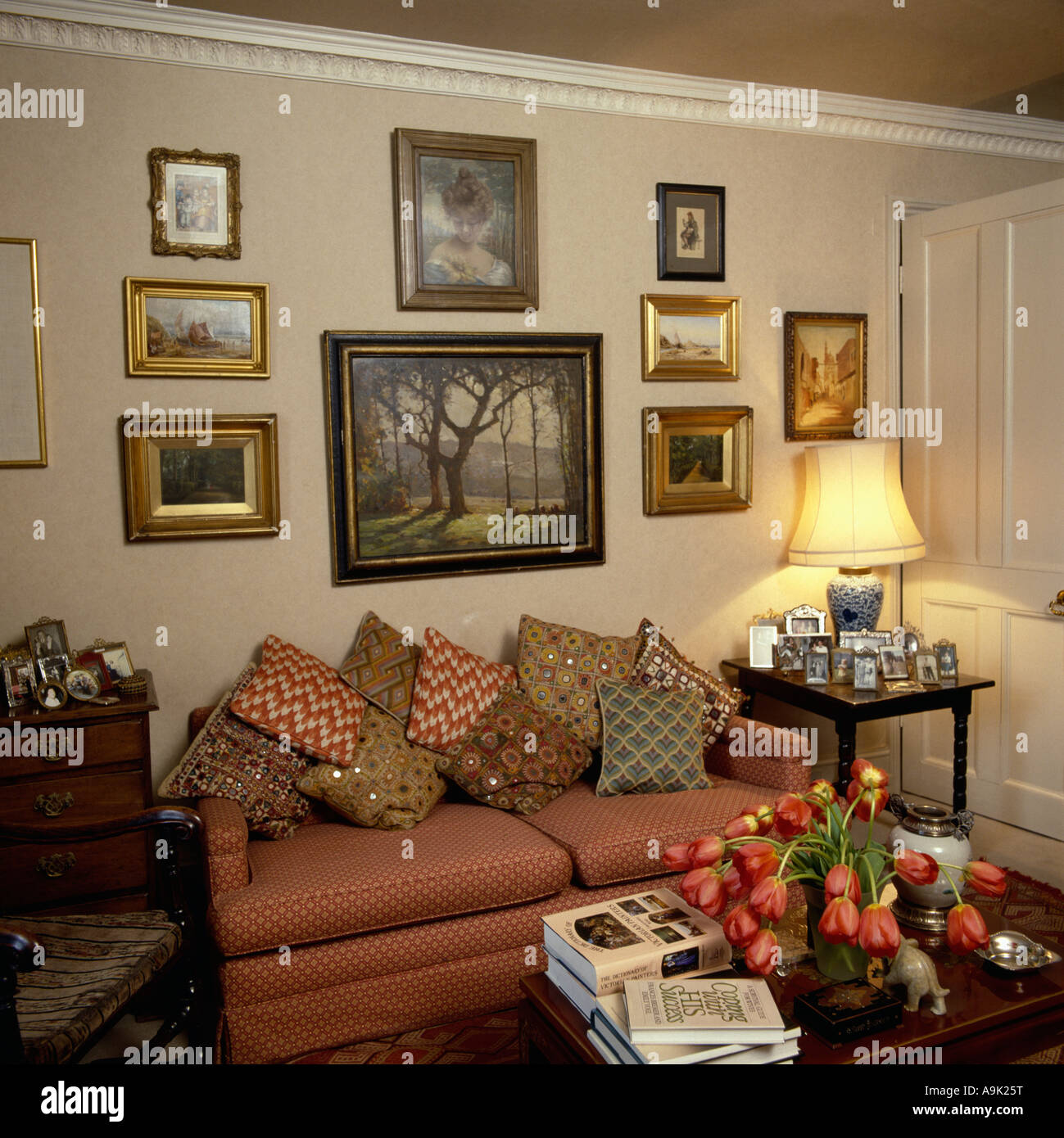 Group Of Pictures Above Terracotta Sofa Piled With