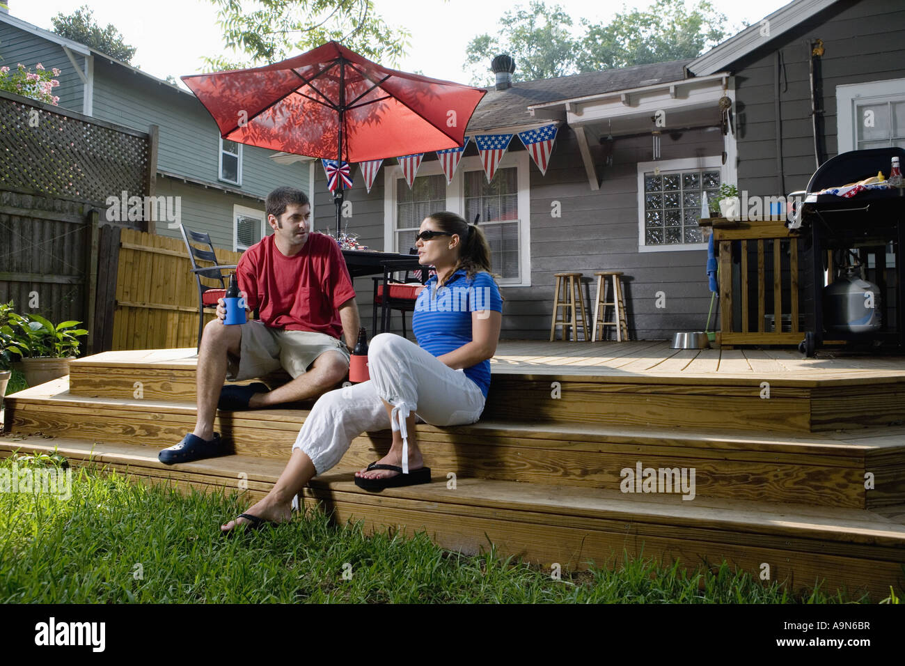 young couple sitting on steps of their backyard patio with 4th of