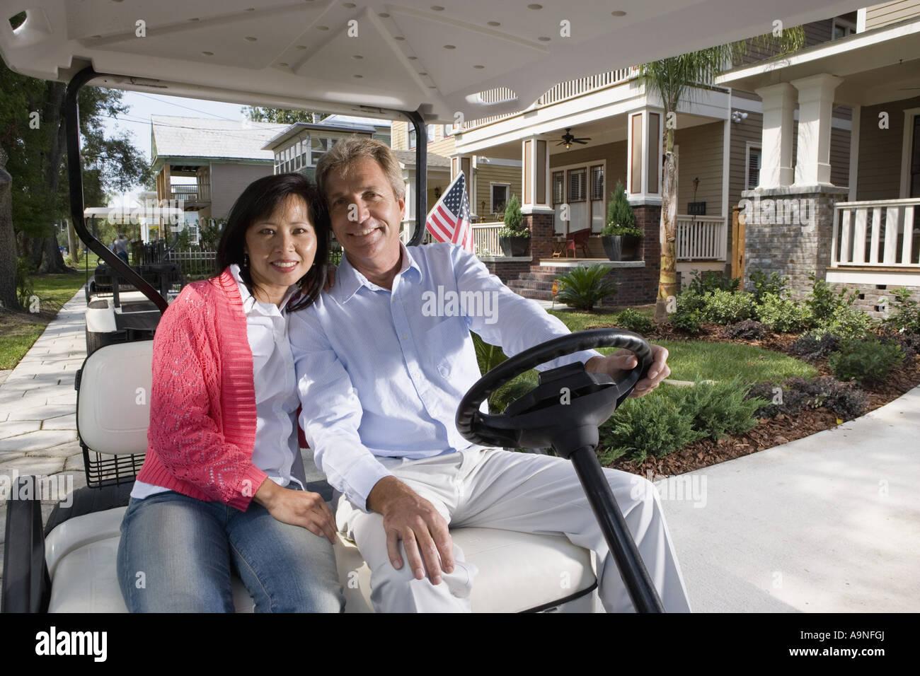 mature couple riding golf cart through the neighborhood stock photo
