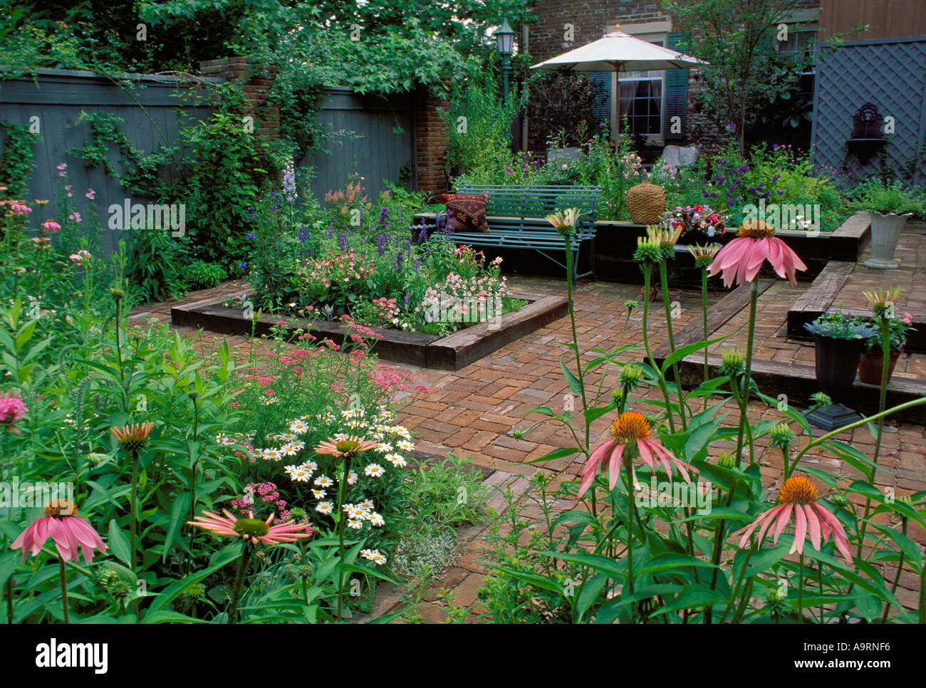 Walled courtyard with raised flower beds and brick walkways Stock ...