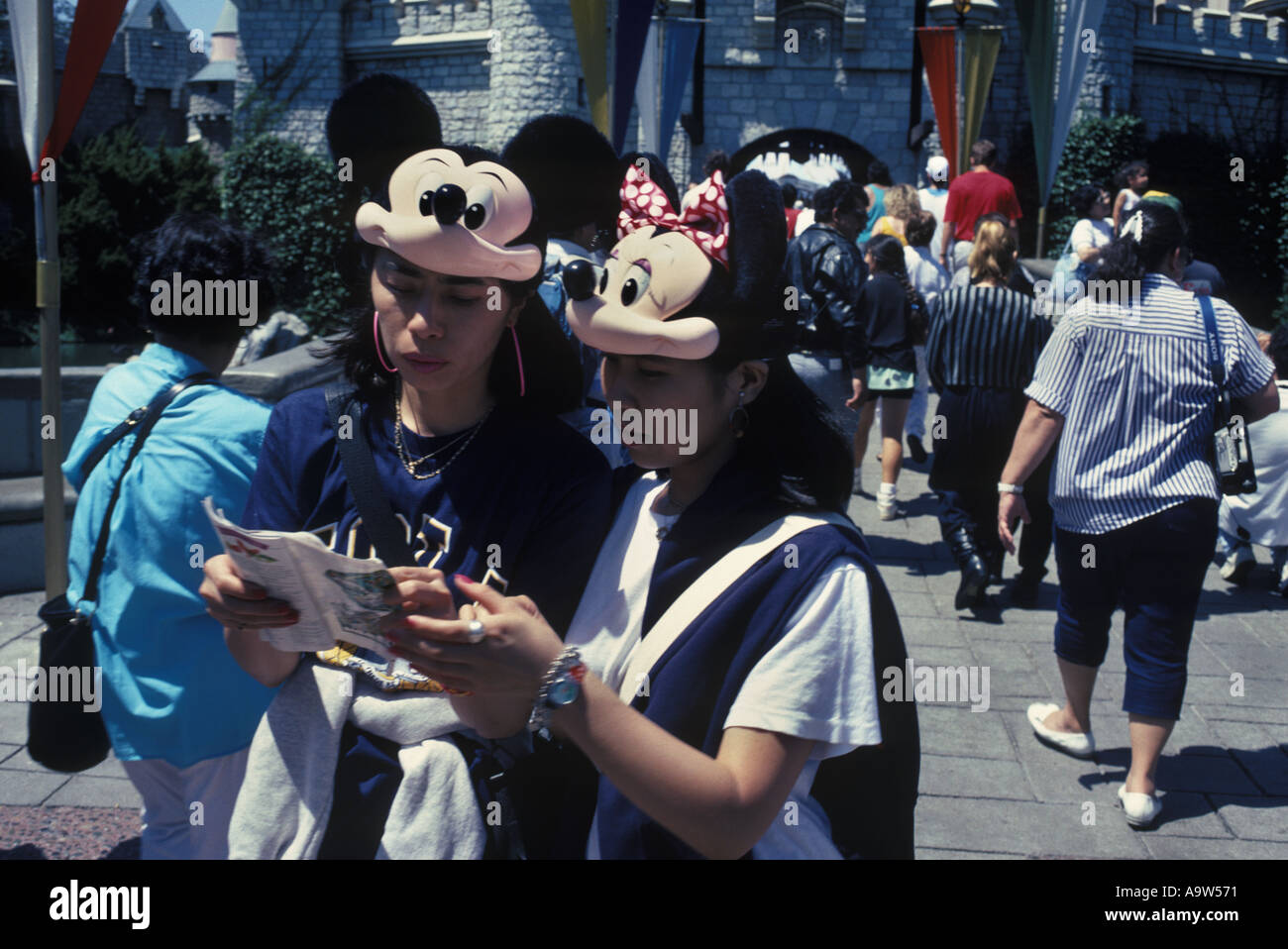 Two japanese women wearing mickey mouse hats looking at map disney two japanese women wearing mickey mouse hats looking at map disney world u s a gumiabroncs Choice Image