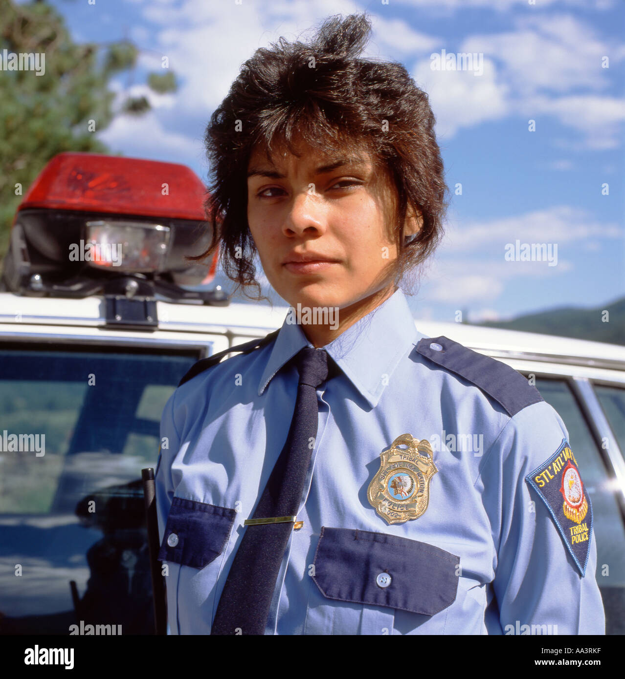 a tribal policewoman in uniform standing by her police car. Black Bedroom Furniture Sets. Home Design Ideas