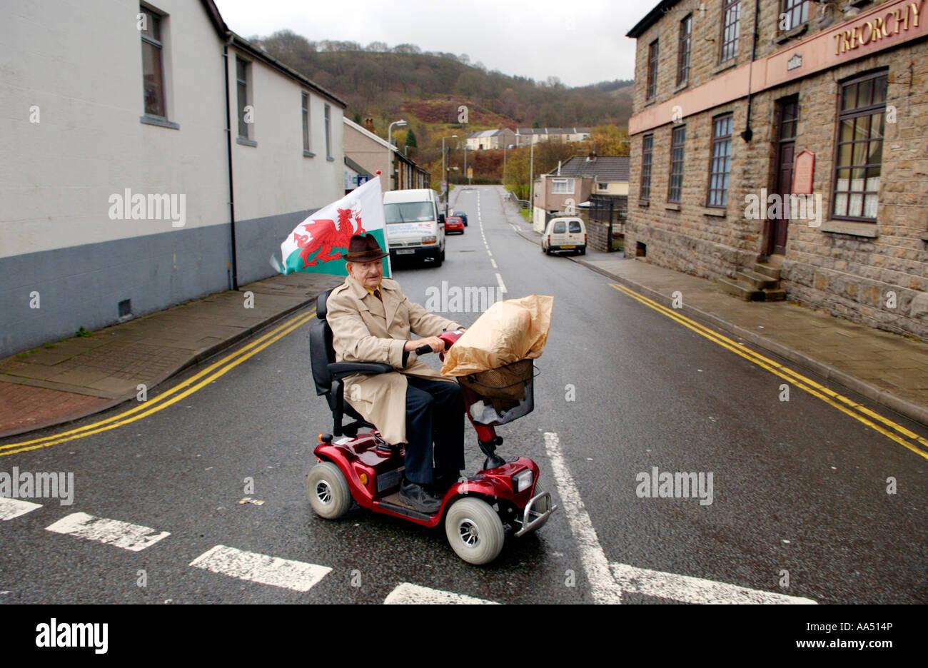 Elderly man on mobility scooter flying red dragon flag for Motorized cart for seniors