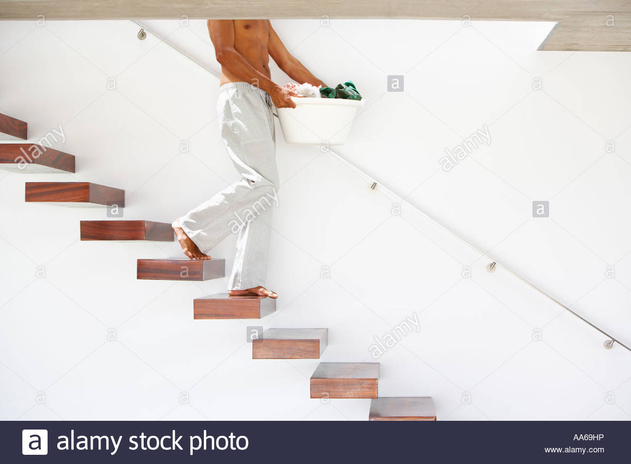 Man Walking Down Stairs With Laundry Basket