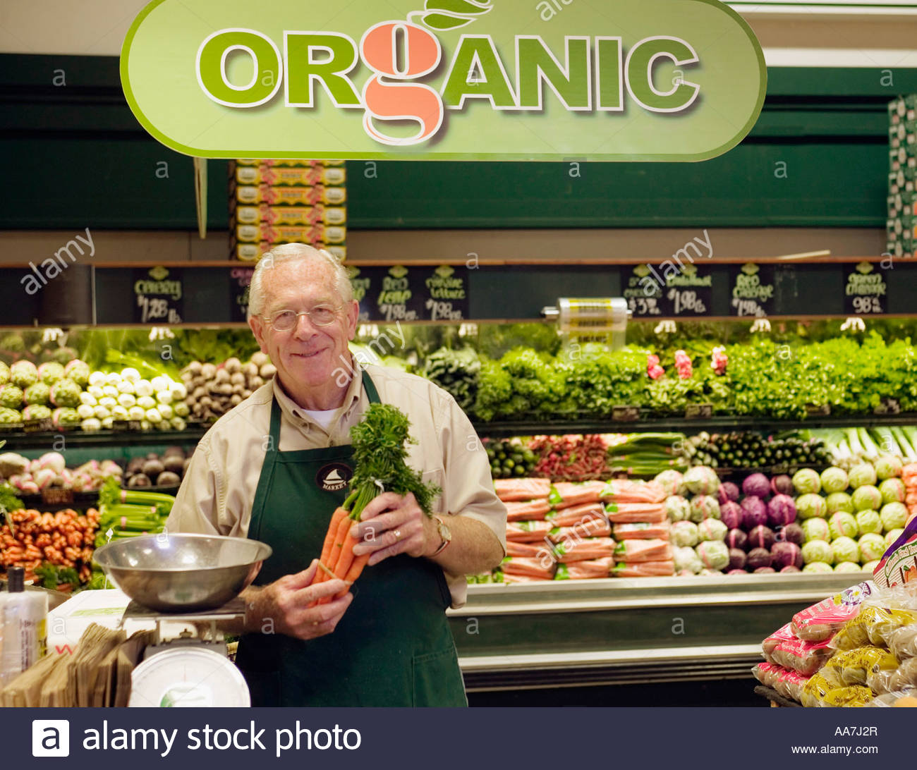 mature grocery clerk working in organic produce aisle of grocery mature grocery clerk working in organic produce aisle of grocery store