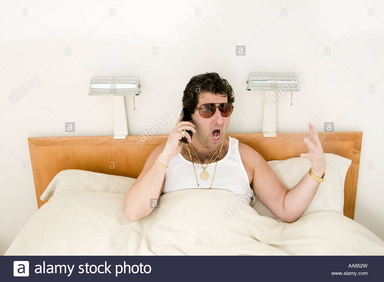 Man talking on cell phone in bed stock photo royalty free for Cell phone bed