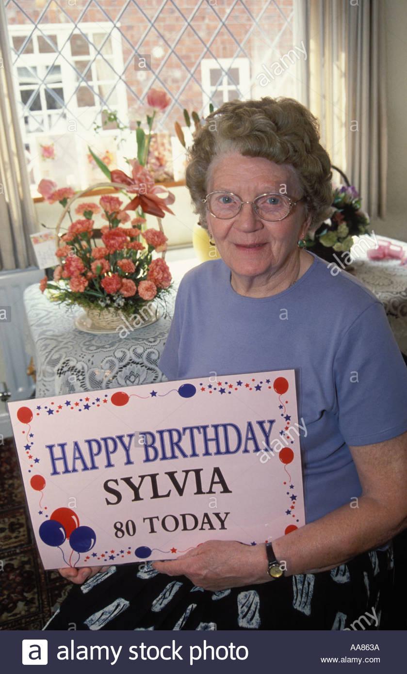 Elderly woman celebrating her 80th birthday with huge birthday