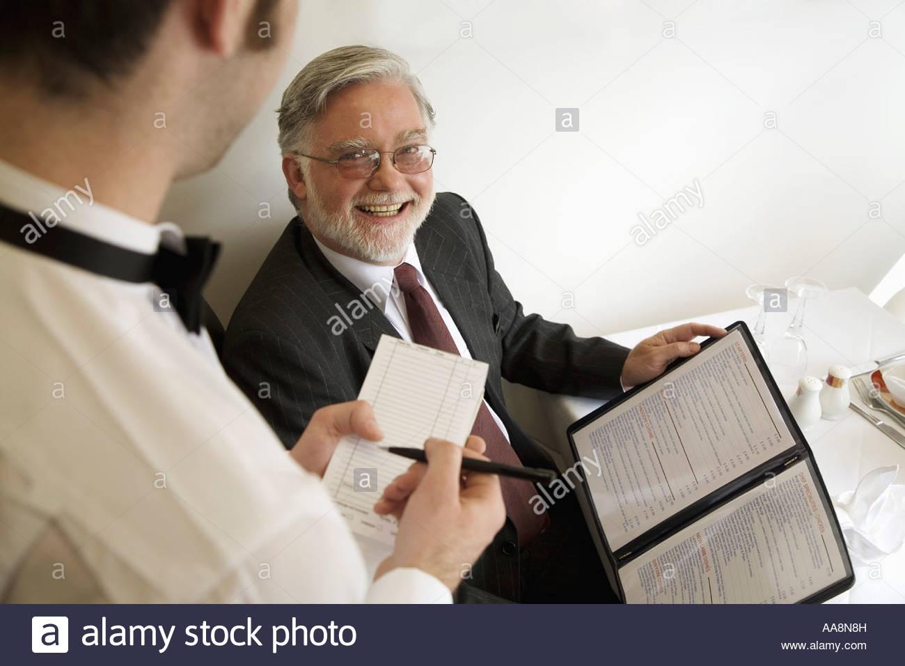 food server taking order from man at restaurant stock photo food server taking order from man at restaurant