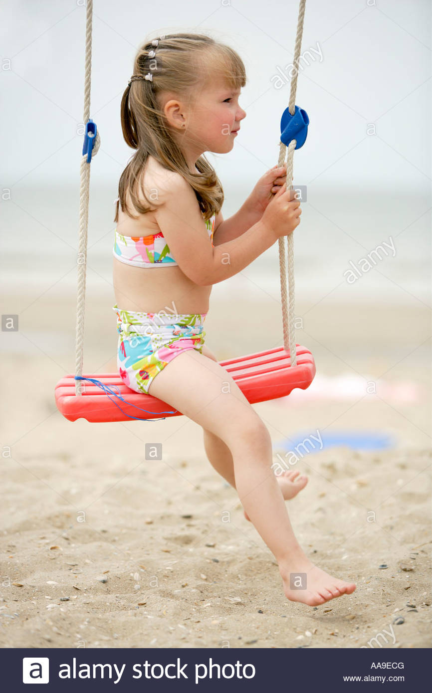 youngster girls Stock Photo - Young girl sitting sideways on swing