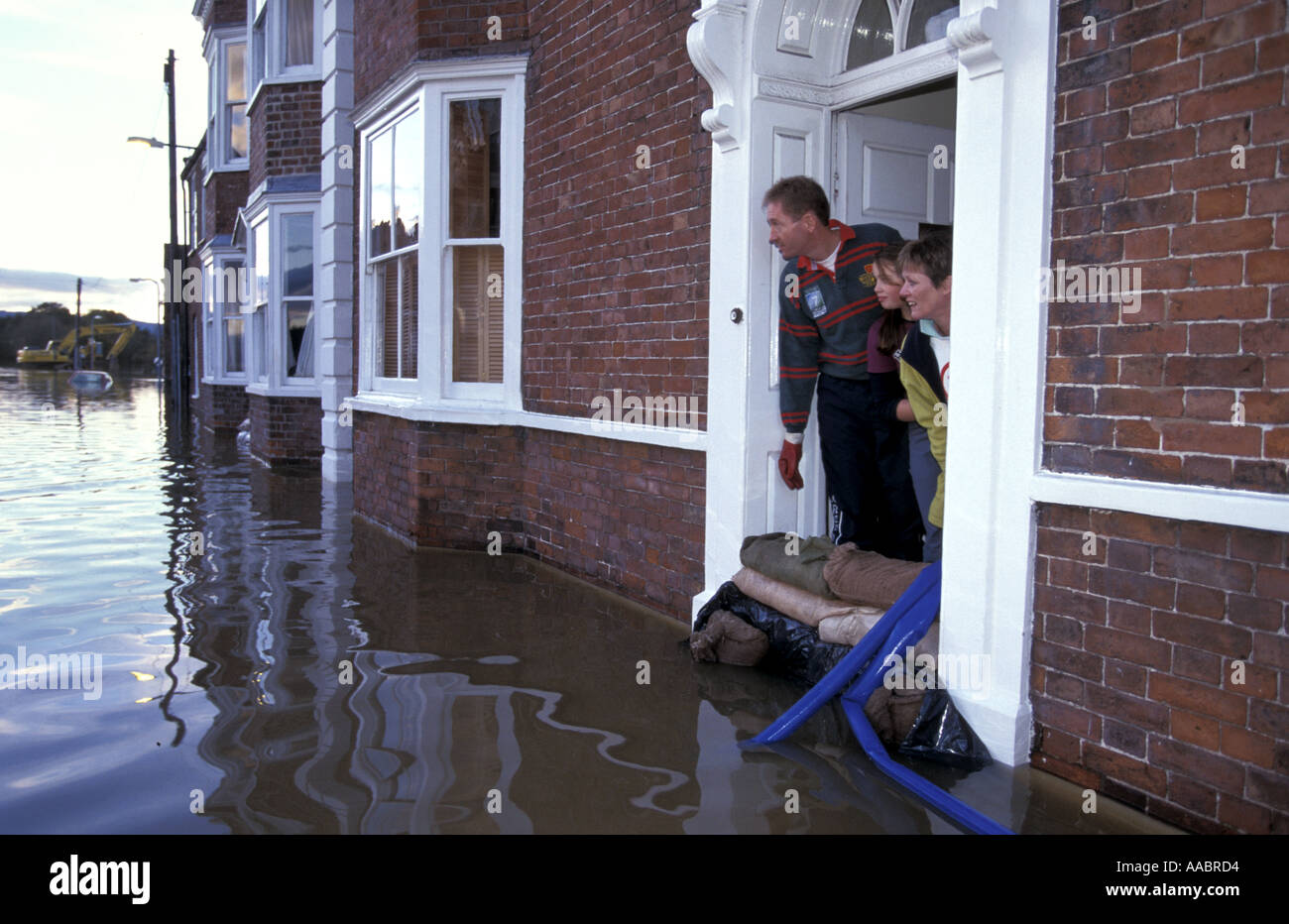 Family in flooded house look out of front door onto flooded street ...