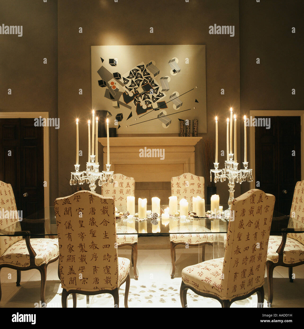 Glass Dining Table With Upholstered Chairs Lit By Candles And Artwork Over Fireplace
