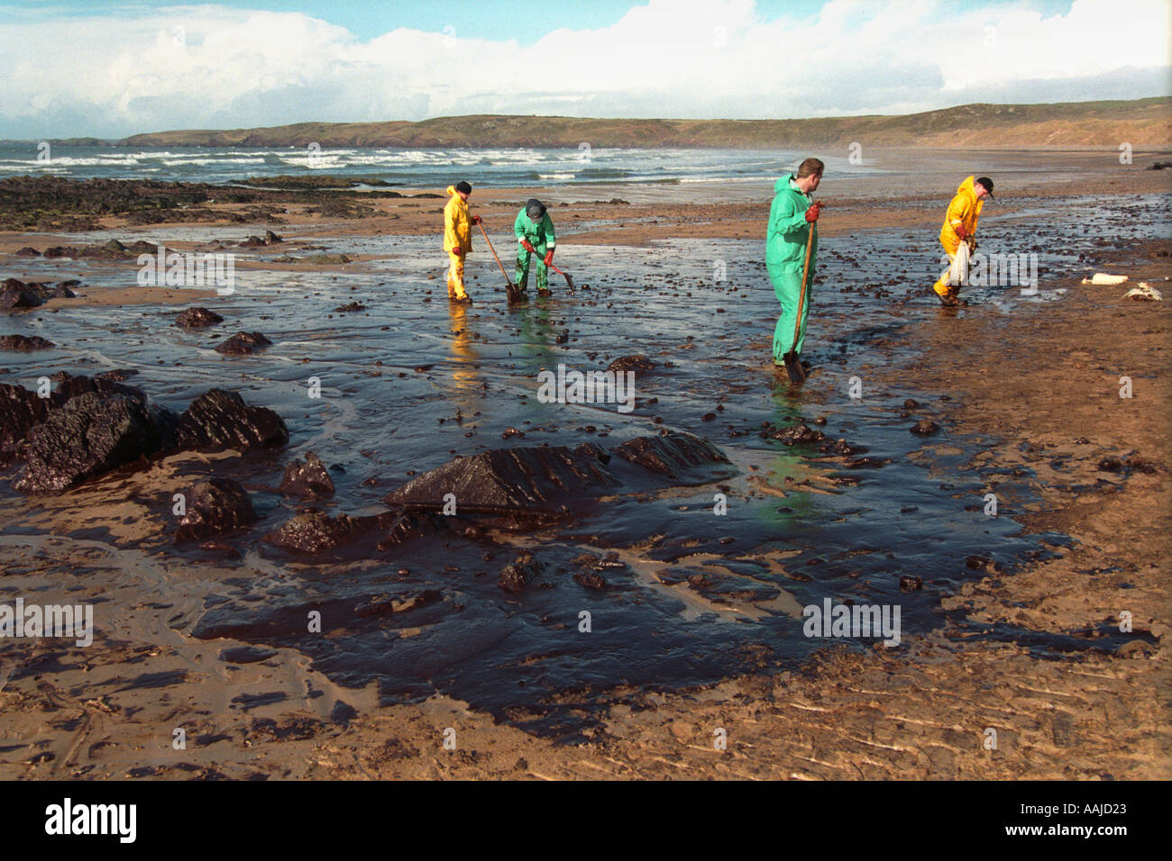 Workmen clean up oil pollution from Sea Empress tanker on beach at ...