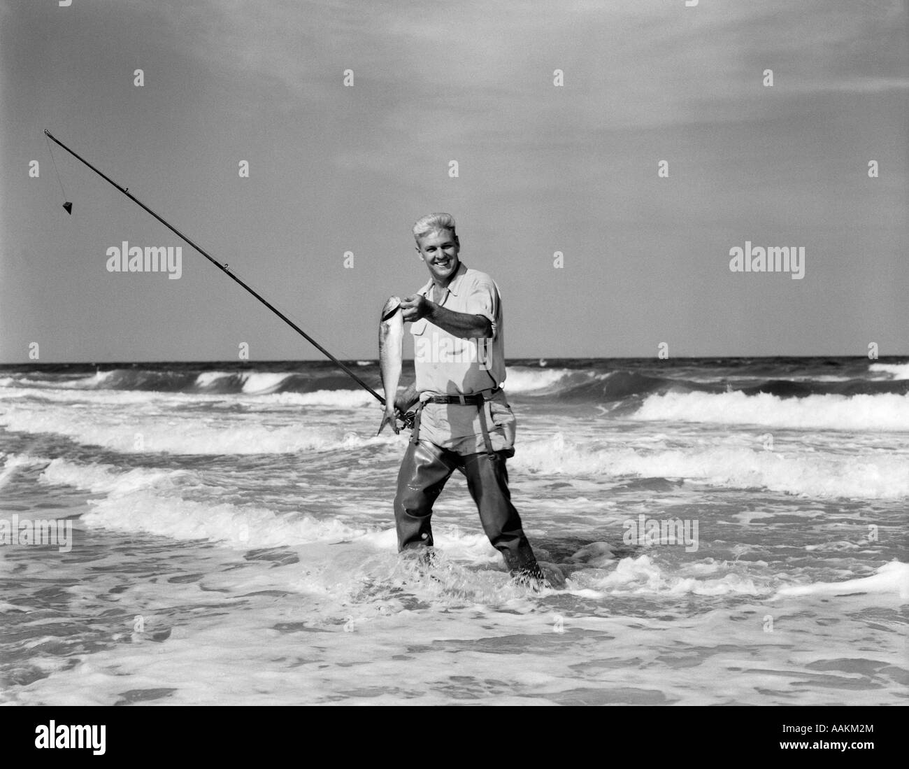 1950s older man standing in surf in waders holding fish in for Surf fishing waders