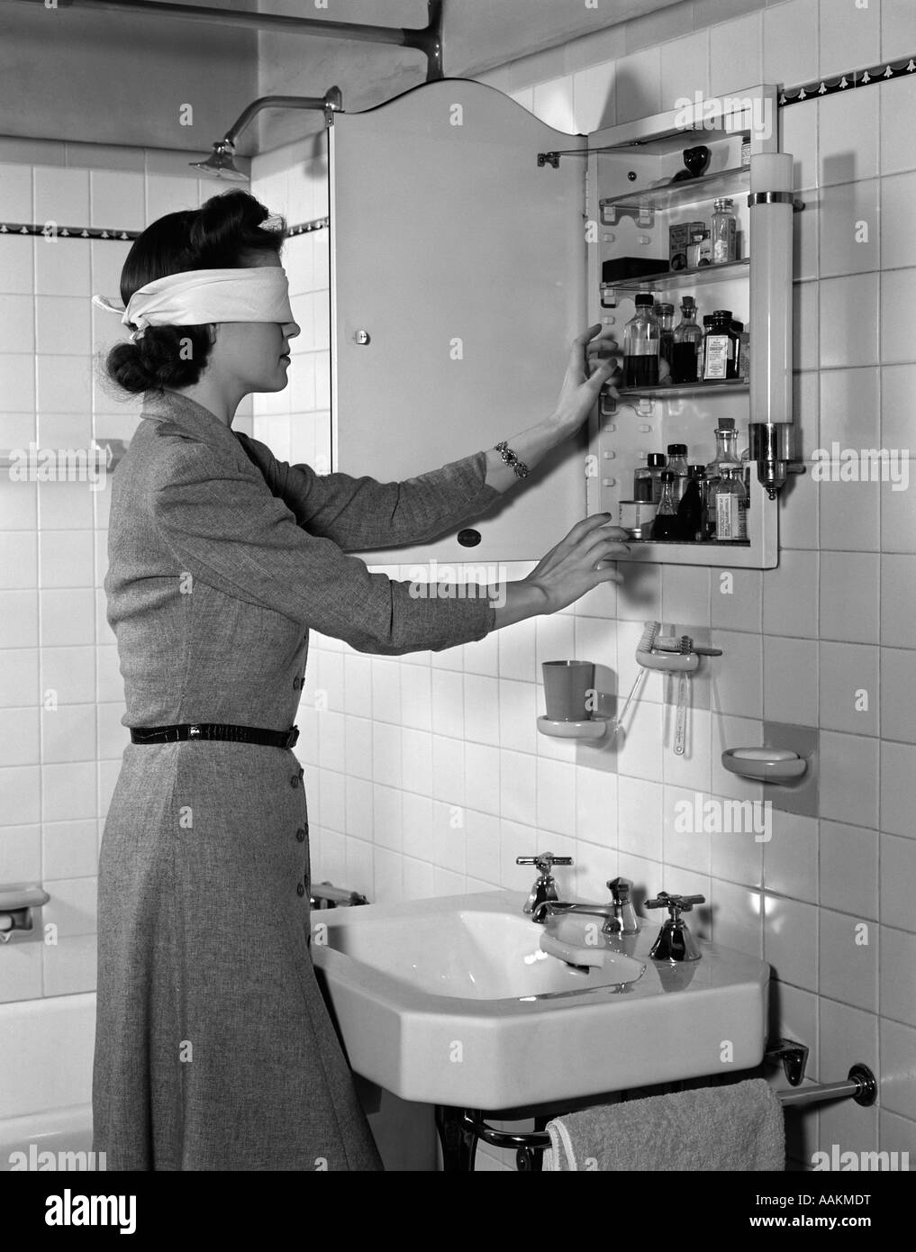 1940s Woman Wearing Blindfold Reaching Into Bathroom Medicine Cabinet   Stock Image