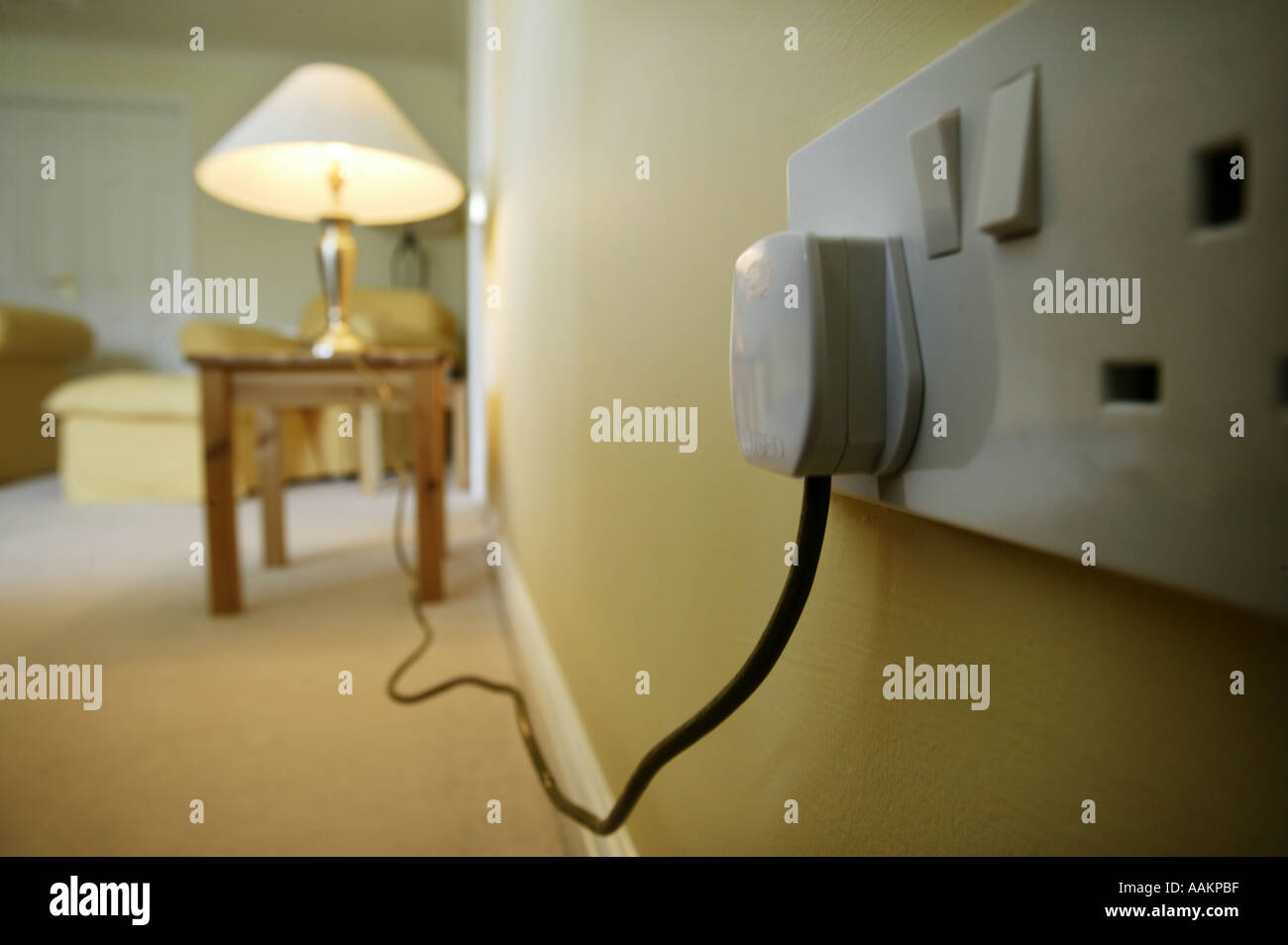 A Table Lamp Plugged Into A Wall Socket In The Uk Stock