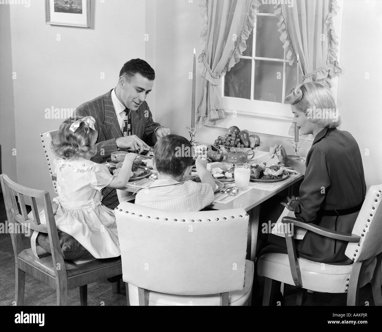 1950s FAMILY OF FOUR EATING DINNER TOGETHER