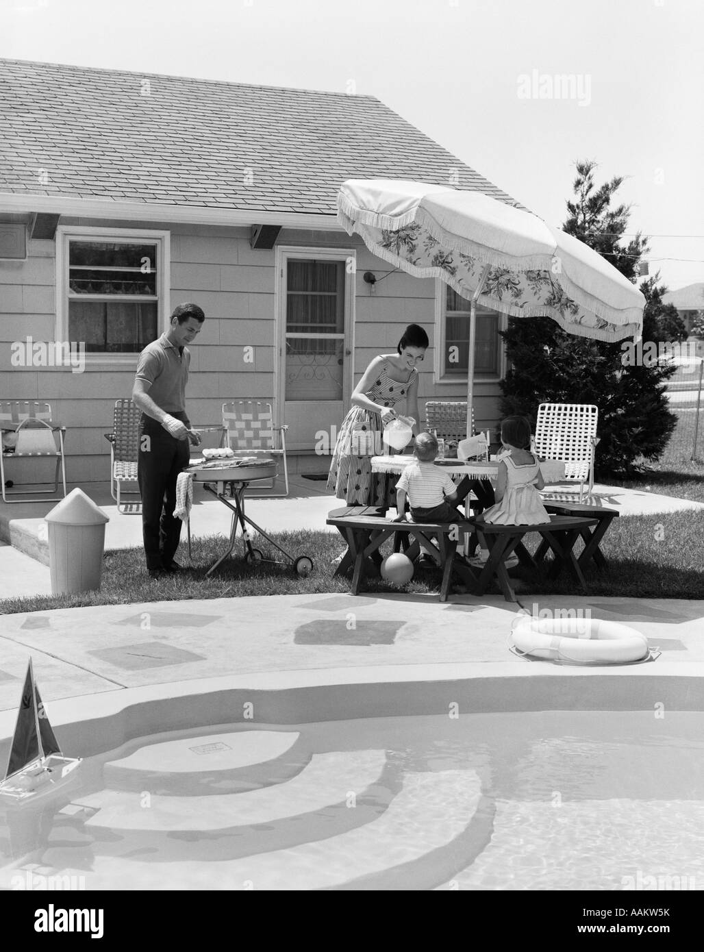 1960s summer outdoor family of four backyard barbeque by pool