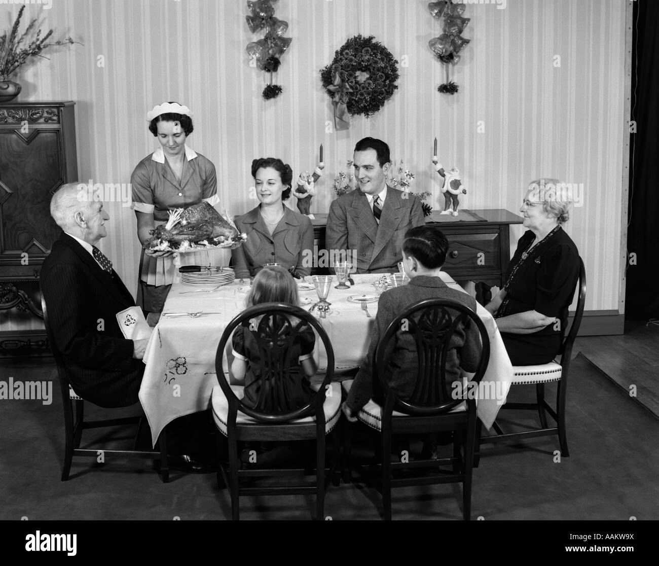 1940s THREE GENERATION FAMILY IN DINING ROOM BEING SERVED CHRISTMAS TURKEY BY MAID