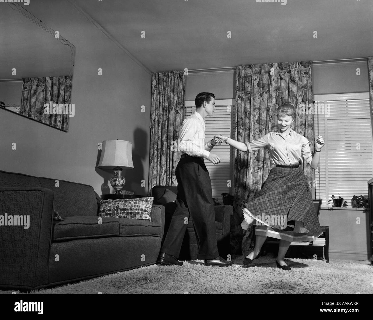Living Room 1950s 1950s teenage couple jitterbug dancing together in living room